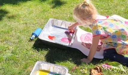 Young girl painting outdoors on the lawn
