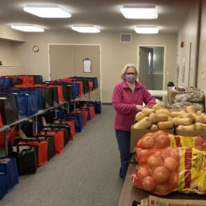 Preparing food bags for distribution - potatoes, onions, other goods