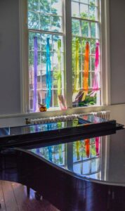 Rainbow-colored streamers hang in the window behind the piano