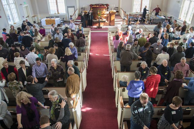 A view of the sanctuary from the balcony with members and friends gathered in conversation