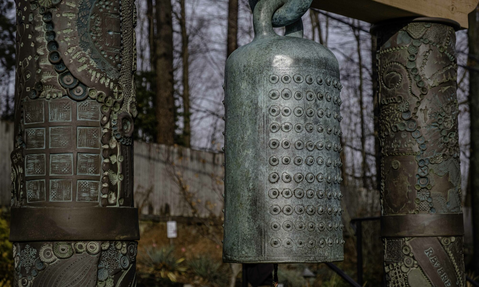 Closeup of the top of the bronze labyrinth bell, suspended between two embellished clay columns
