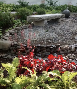 Fountain, bench, and plantings along one edge of the lower yard